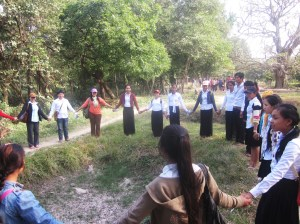 Students forming a circle around one of the mass graves at the Killing Fields